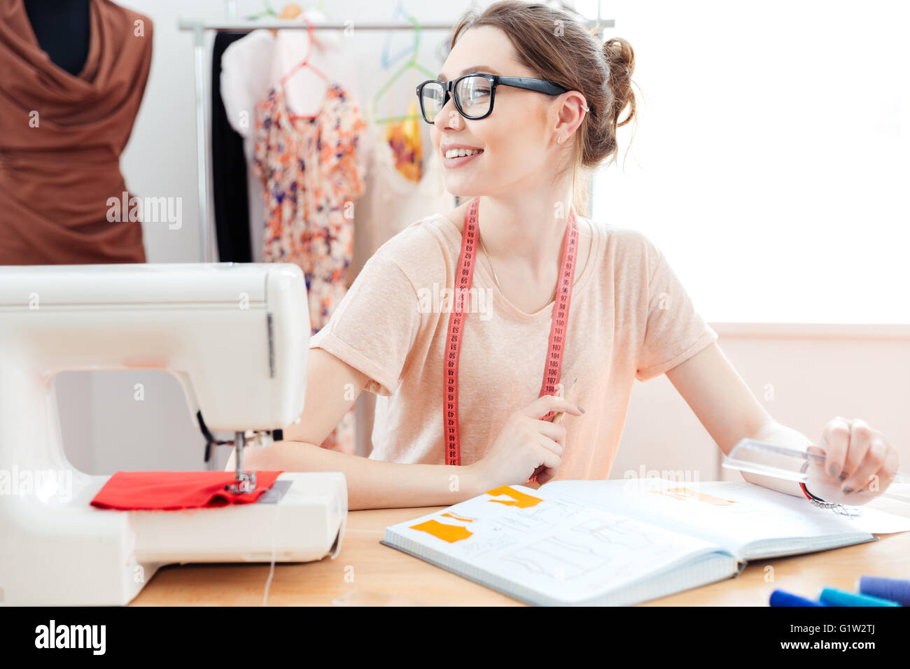 Smiling pretty young professional seamstress at work - Stock Image