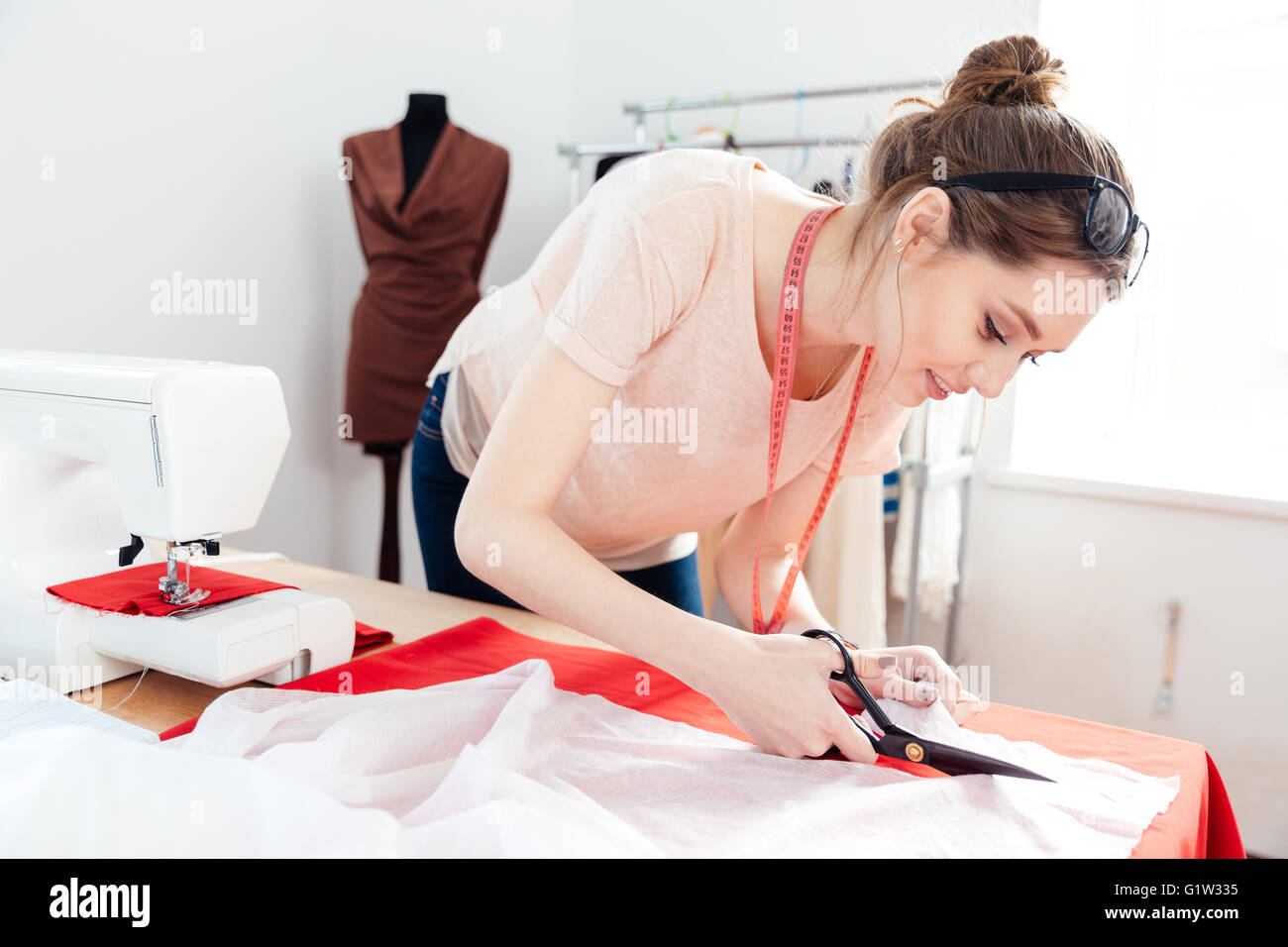 Beautiful focused young woman fashion designer cutting white fabric in studio - Stock Image