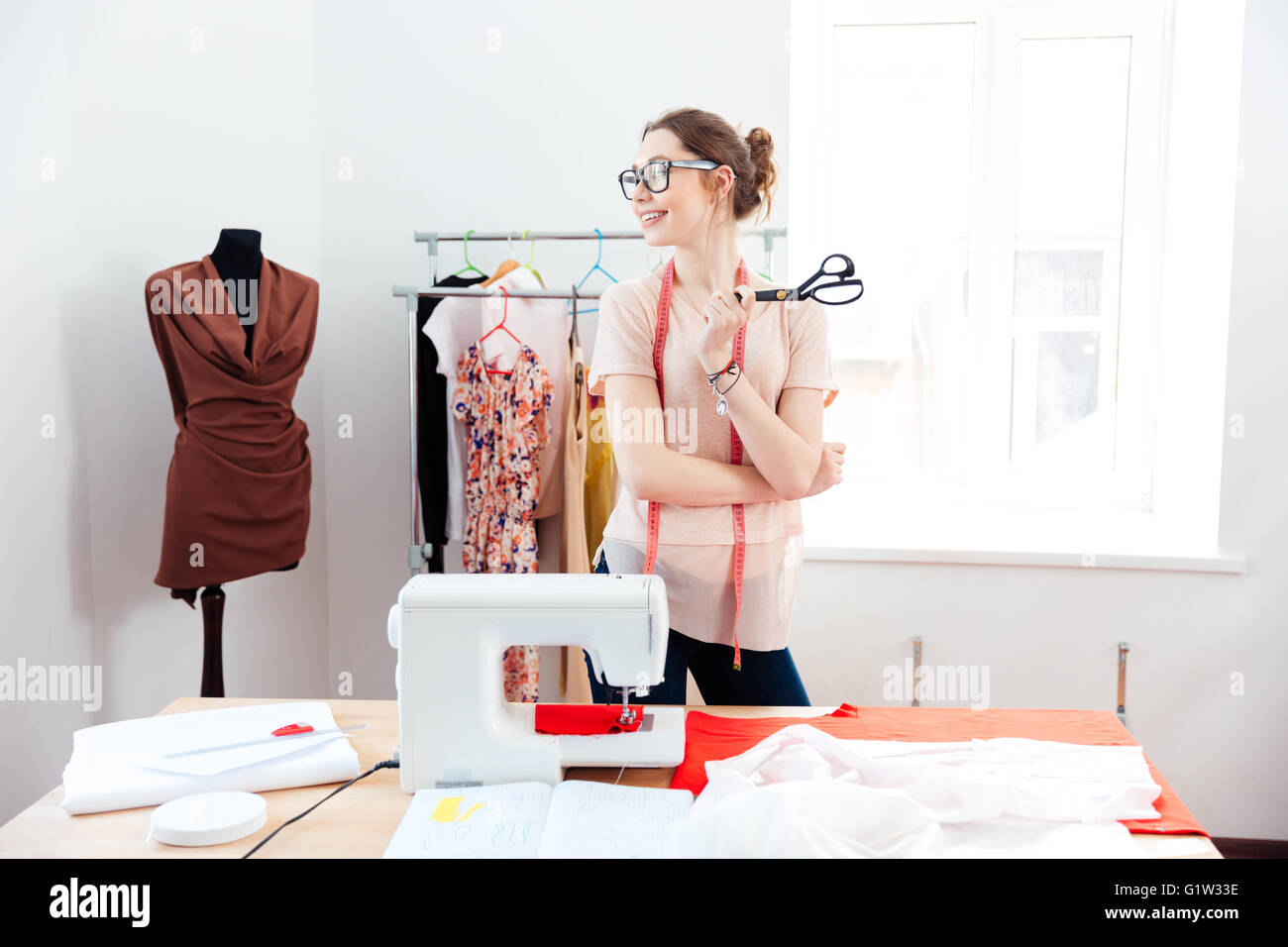 Cheerful attractive young woman seamstress with scissors standing and smilig in design studio - Stock Image