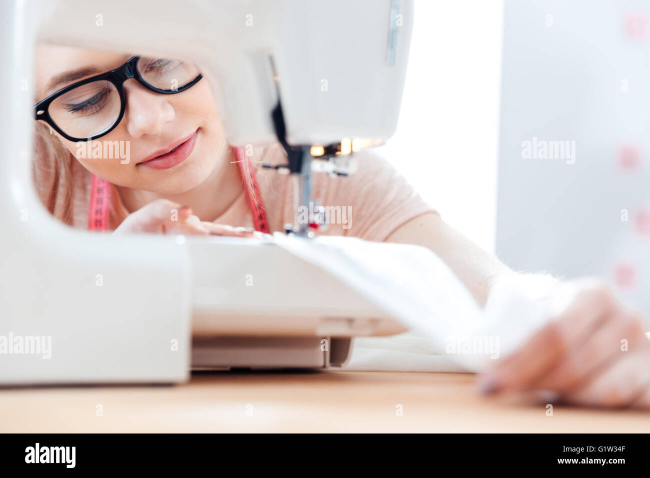 Concentrated charming young seamstress at work with cloth fabric - Stock Image
