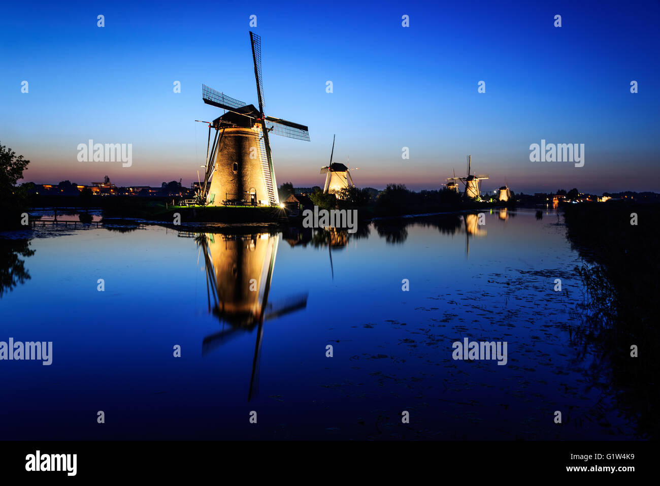 Historic illuminated windmills in Kinderdijk with reflection in the water of the canal under a Blue Hour sky in - Stock Image