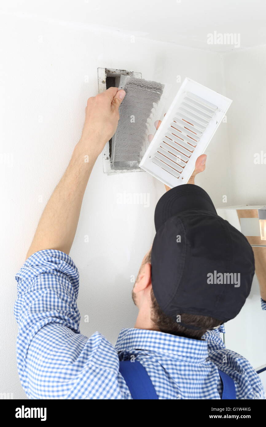 A Craftsmen changing a Ventilation filter 3 - Stock Image