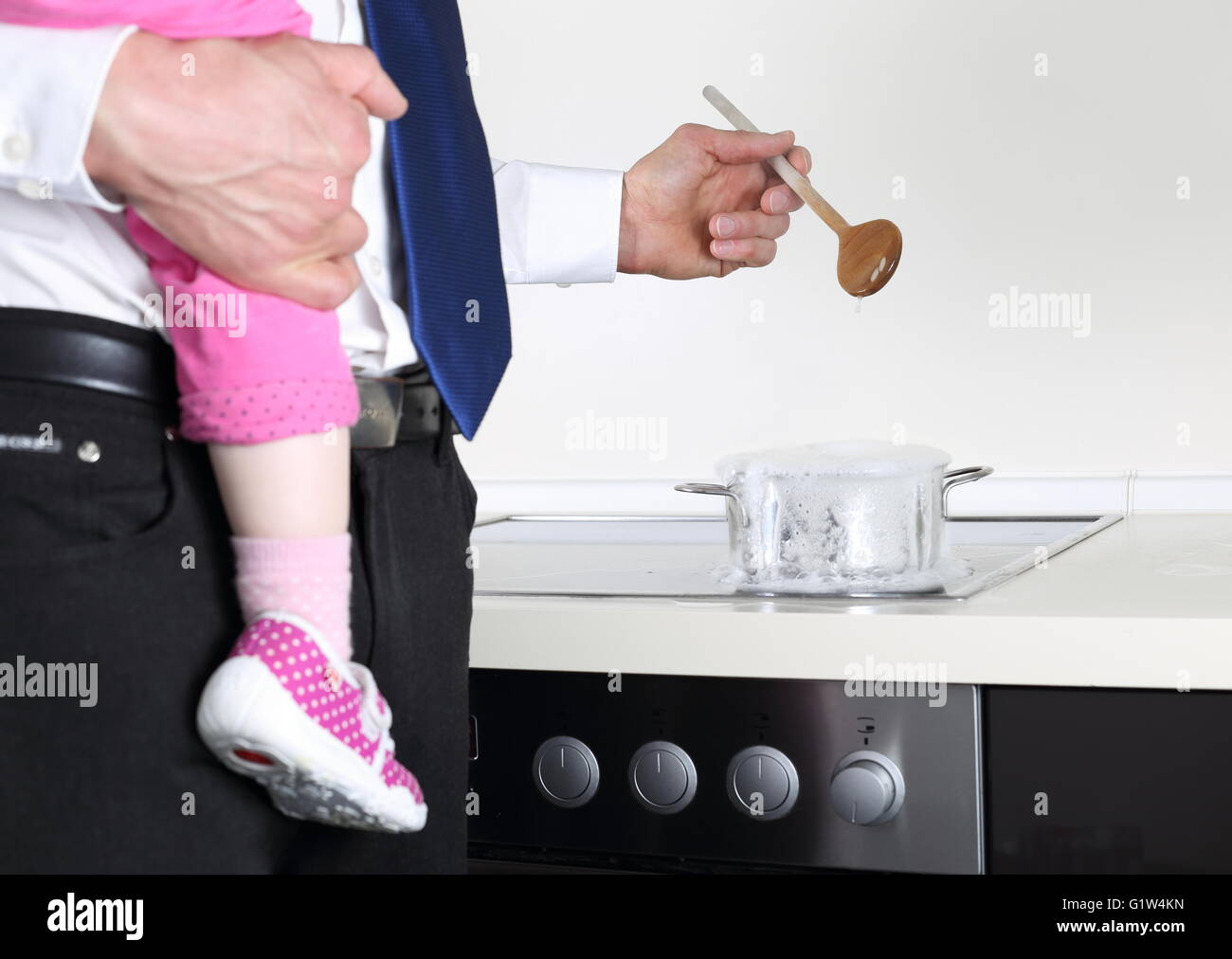 A Businessman cooking with Baby on arm - Stock Image