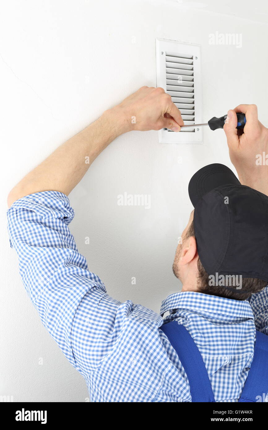 A Craftsmen changing a Ventilation filter 1 - Stock Image