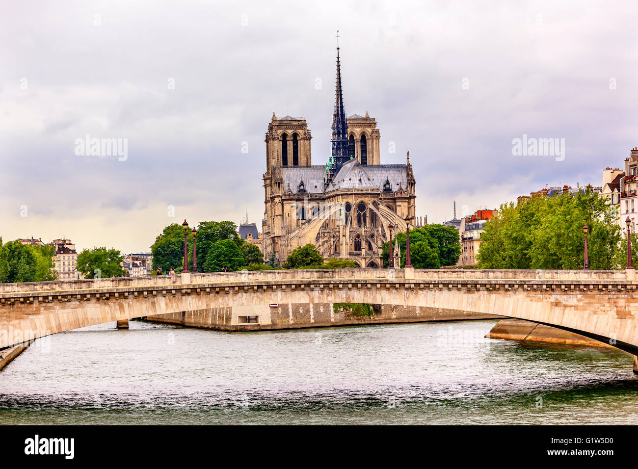 Flying Buttresses Spires Towers Seine River Bridge Overcast Skies Notre Dame Cathedral Paris France. - Stock Image