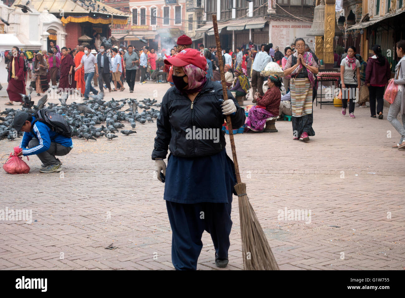 Woman with a broom walking at the Boudhanath Stupa, a buddhist temple in Kathmandu, Nepal - Stock Image