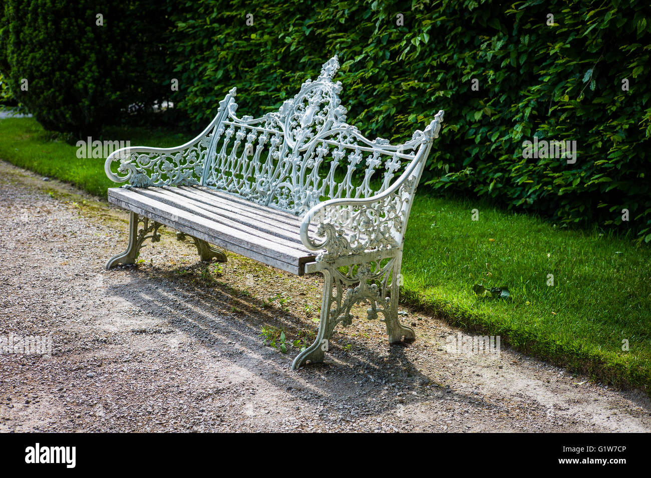 Old cast iron bench seat in garden open to the public in Cumbria UK Stock Photo