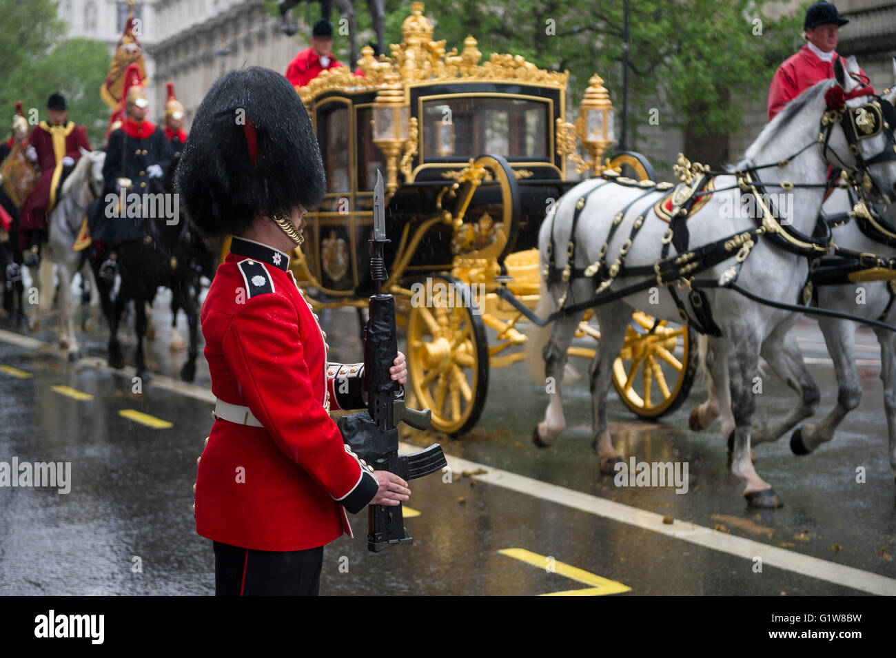 LONDON - MAY 18, 2016: Guard stands at attention as the horse-drawn Diamond Jubilee State Coach carrying Queen Elizabeth - Stock Image