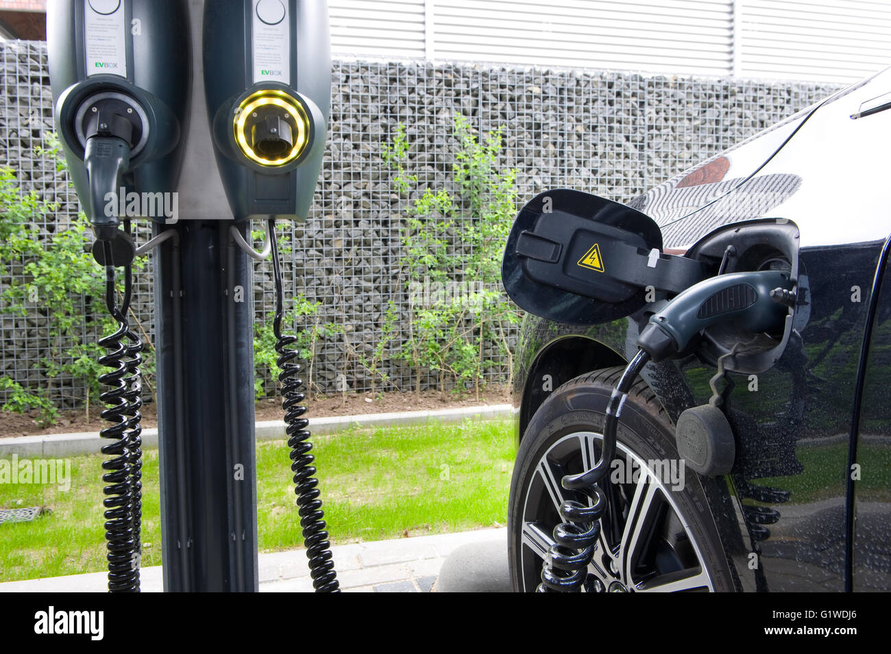 An electric car is parked at a parking spot and is being recharged at a power station. - Stock Image