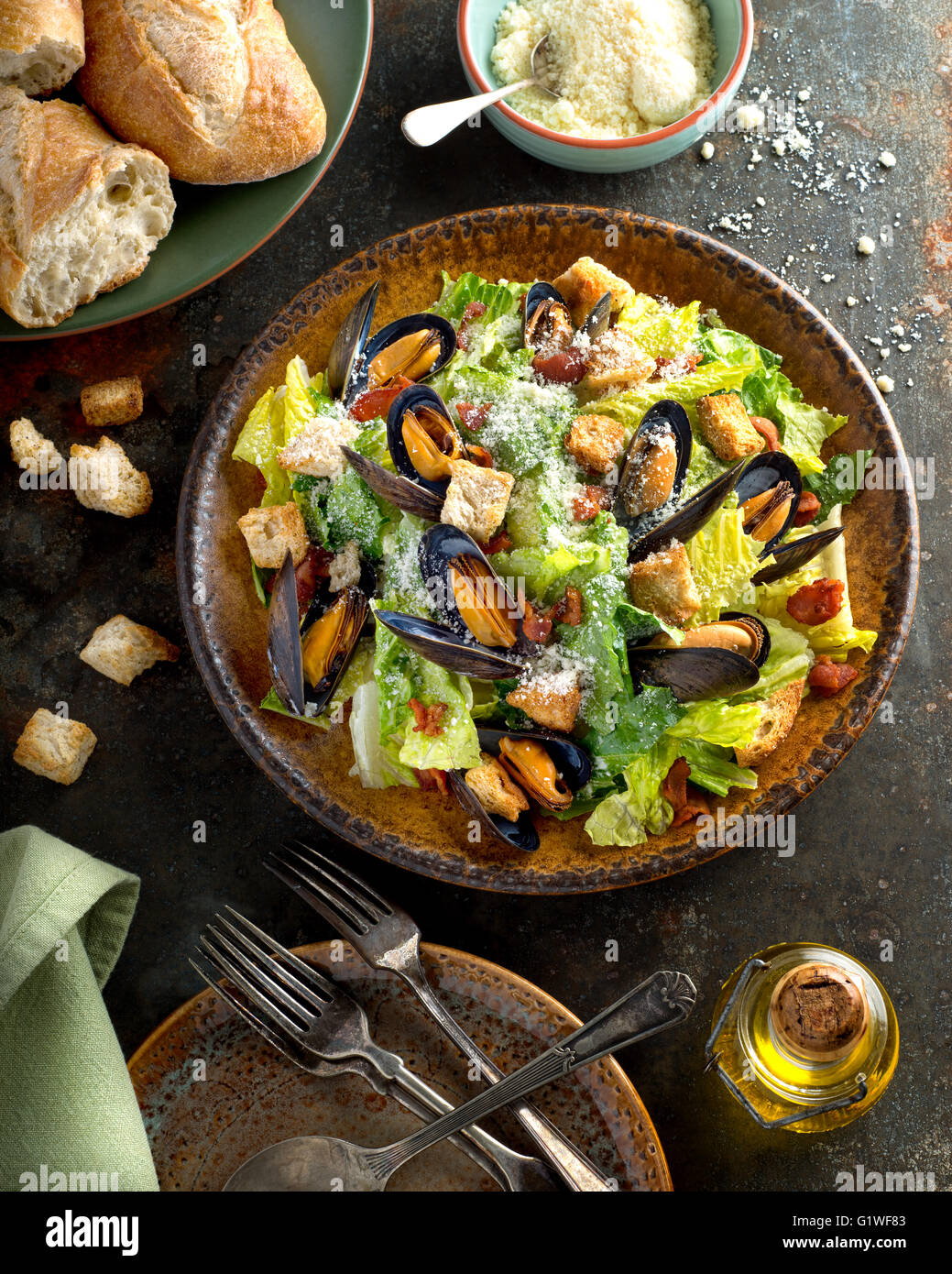 A delicious caesar salad with mussels, romaine lettuce, bacon, croutons, and parmesan cheese. - Stock Image