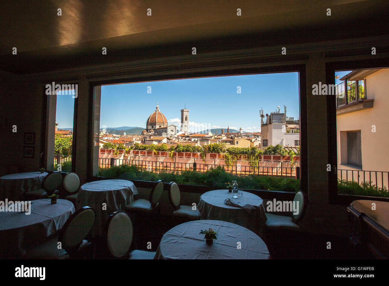 view of  Brunelleschi dome, Duomo from restaurant Florence  empty restaurant  empty tables dark interior bright - Stock Image