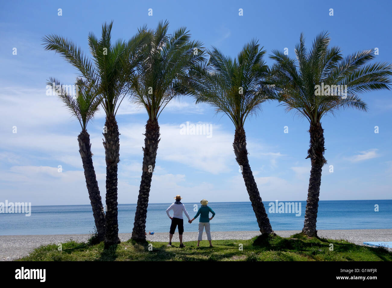 Palm trees and a couple on Herradura beach in Spain Europe - Stock Image