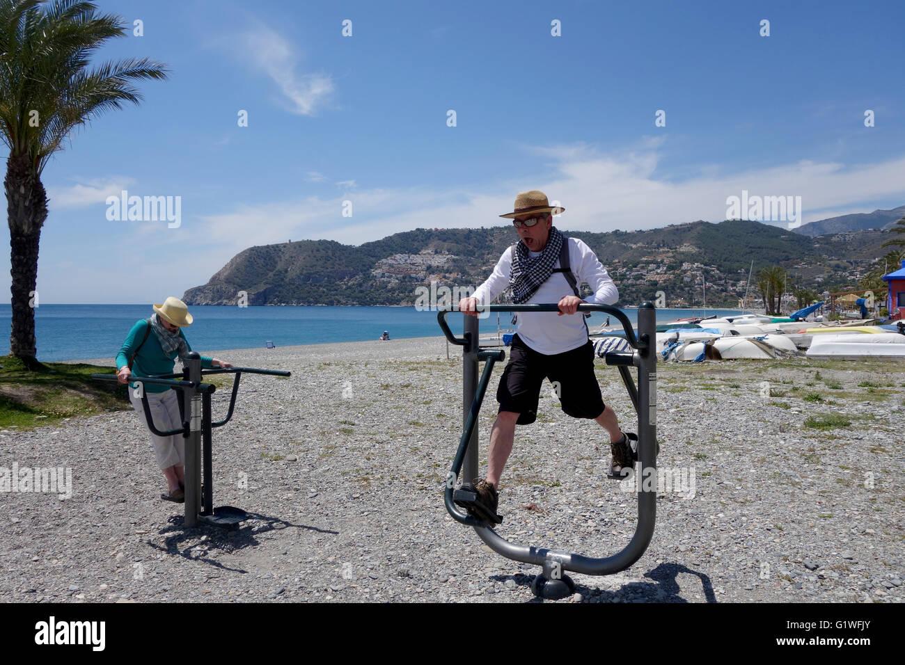 People using public keep fit exercise machines on Herradura beach in Spain Europe - Stock Image