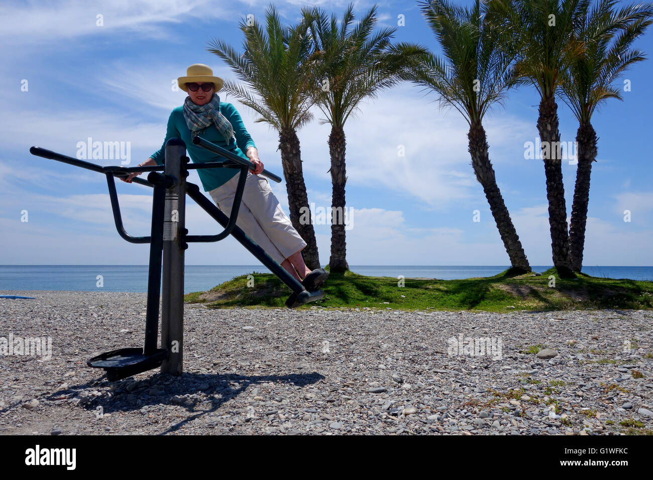 Woman using public keep fit exercise machines on Herradura beach in Spain Europe - Stock Image