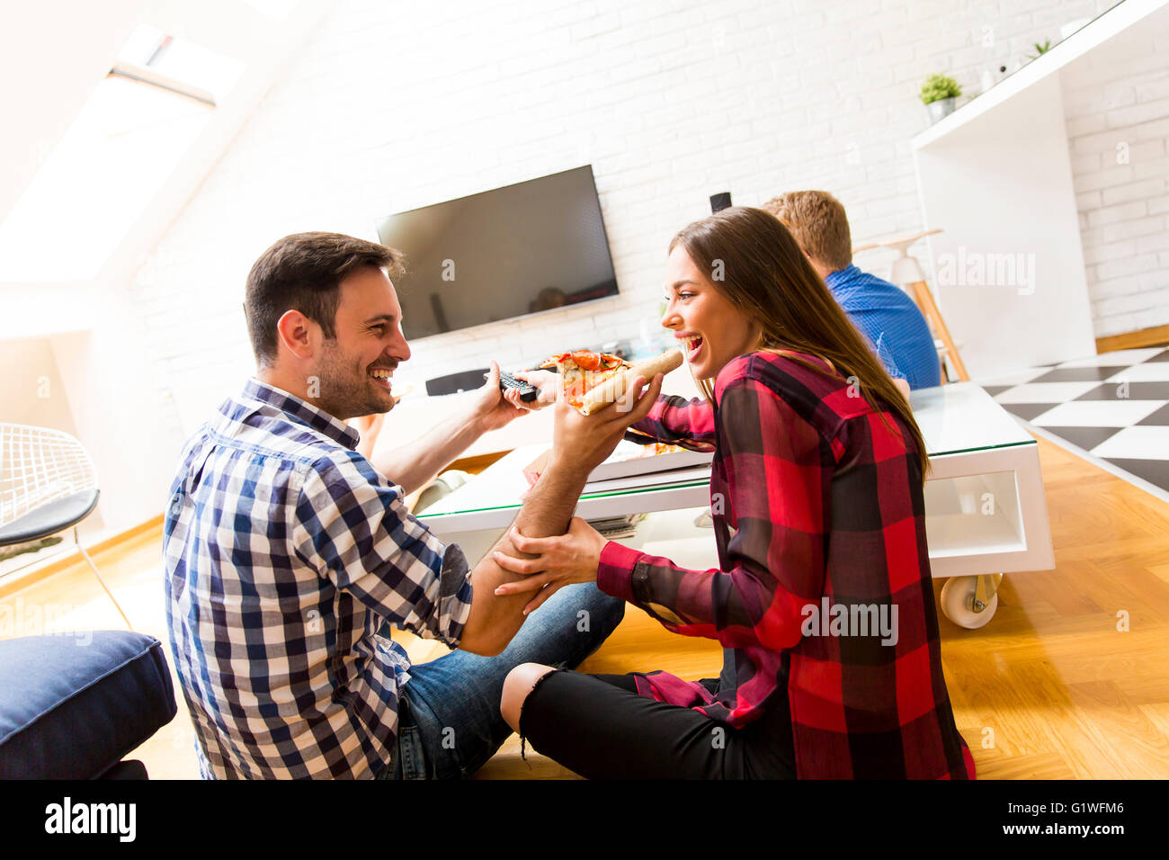 Couple eating pizza and a man holding tv remote control - Stock Image