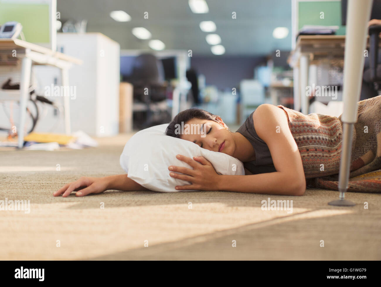 Businesswoman sleeping with pillow on office floor Stock Photo ...