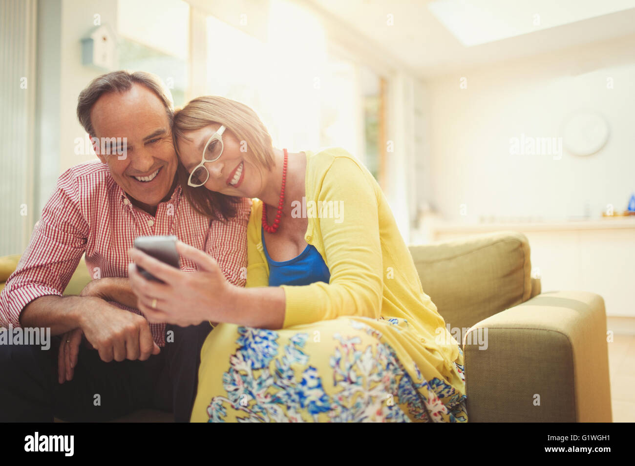 Smiling mature couple texting with cell phone in living room - Stock Image