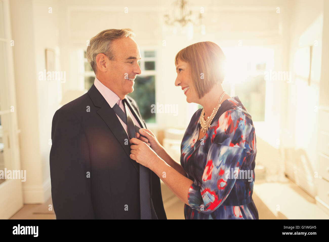 Smiling wife tying husband's tie - Stock Image