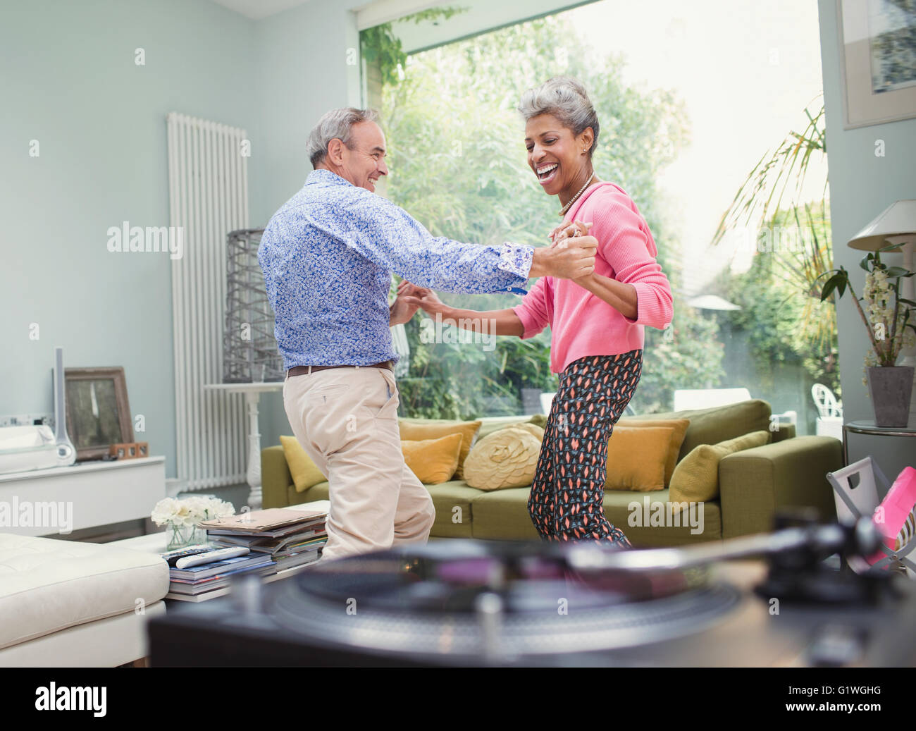 Playful mature couple dancing in living room Stock Photo