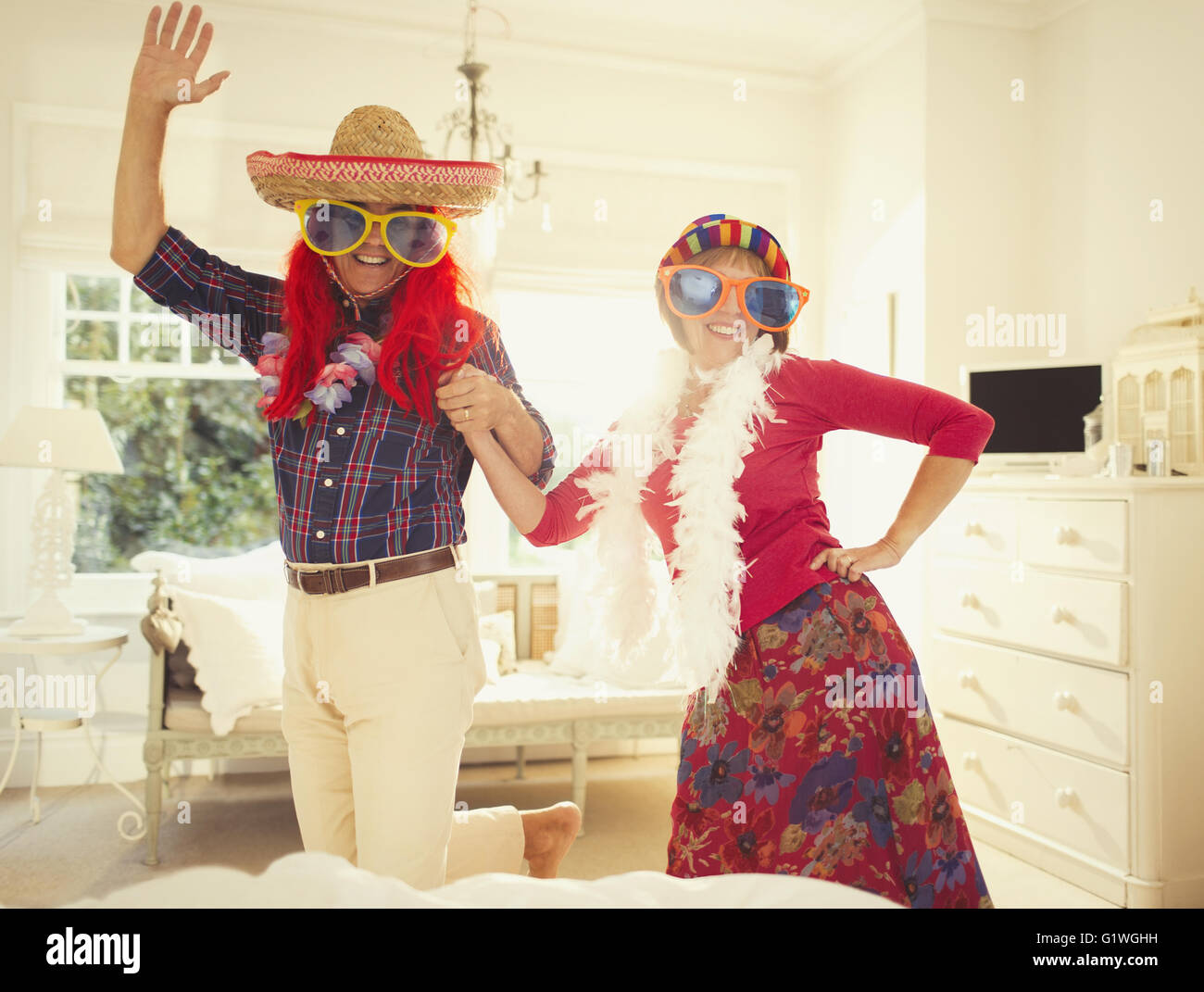 Portrait silly mature couple dancing in costumes - Stock Image