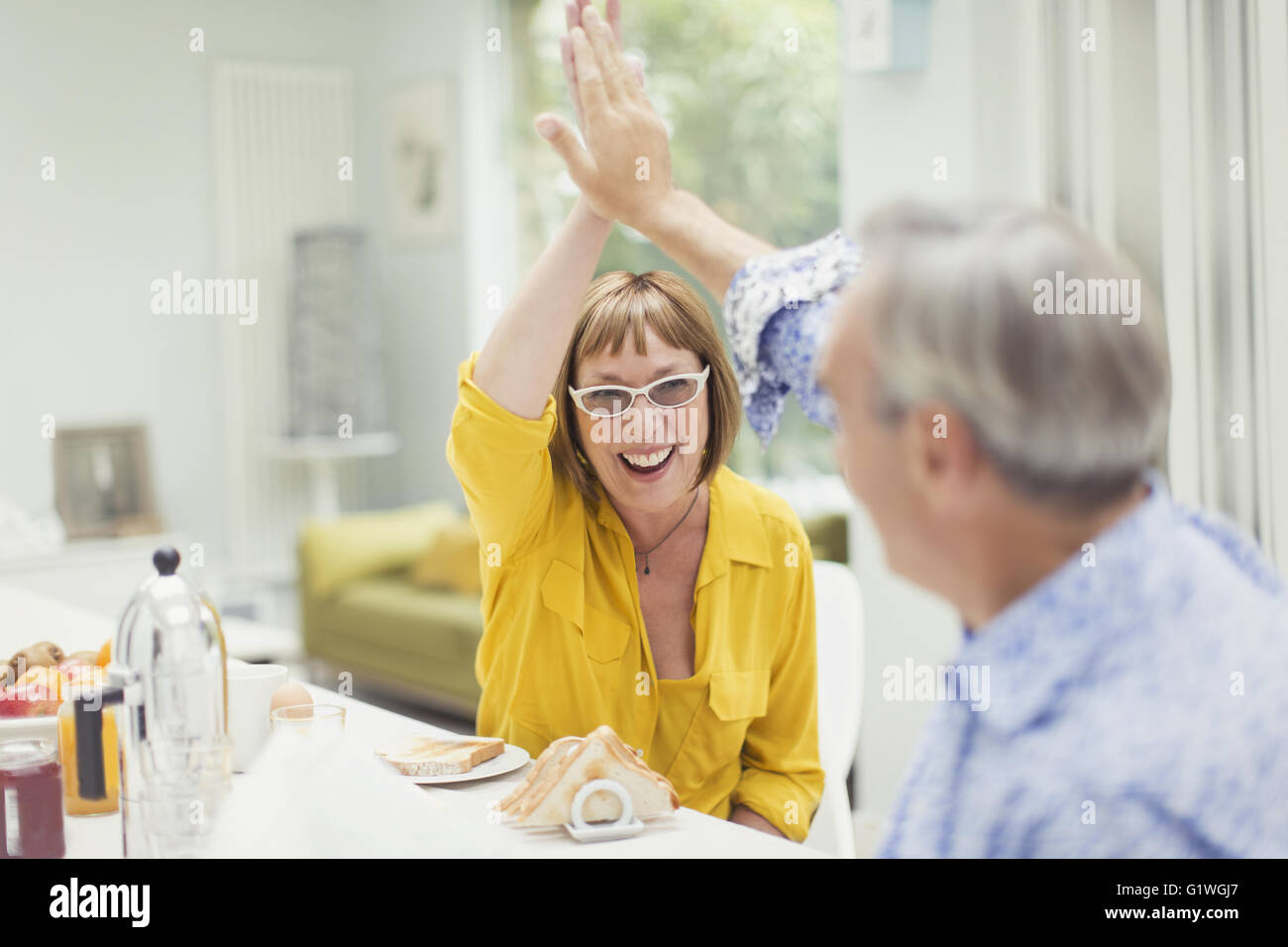 Enthusiastic mature couple high-fiving at breakfast - Stock Image