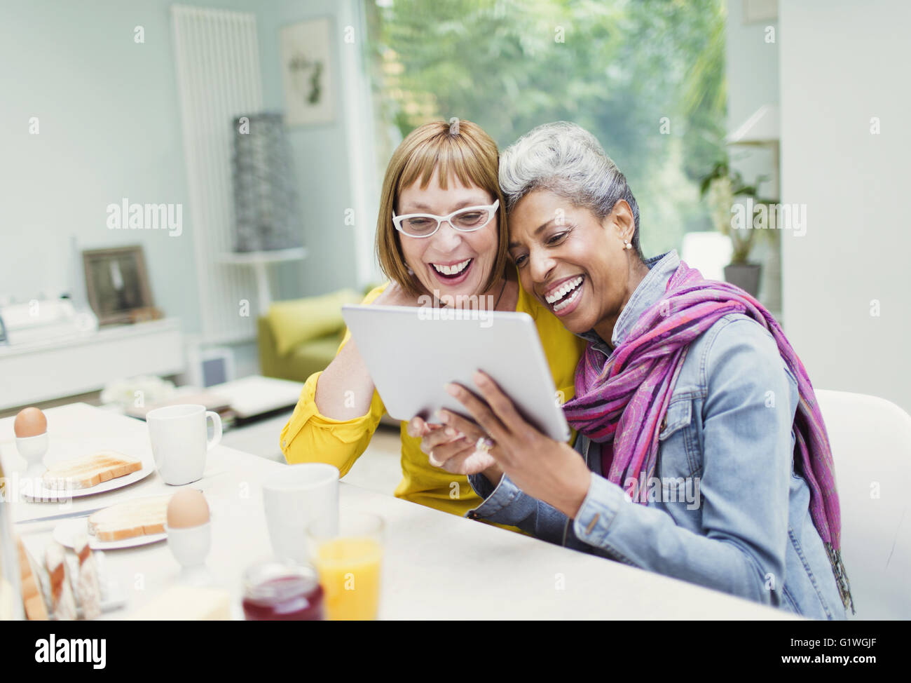 Laughing mature women sharing digital tablet at breakfast table - Stock Image