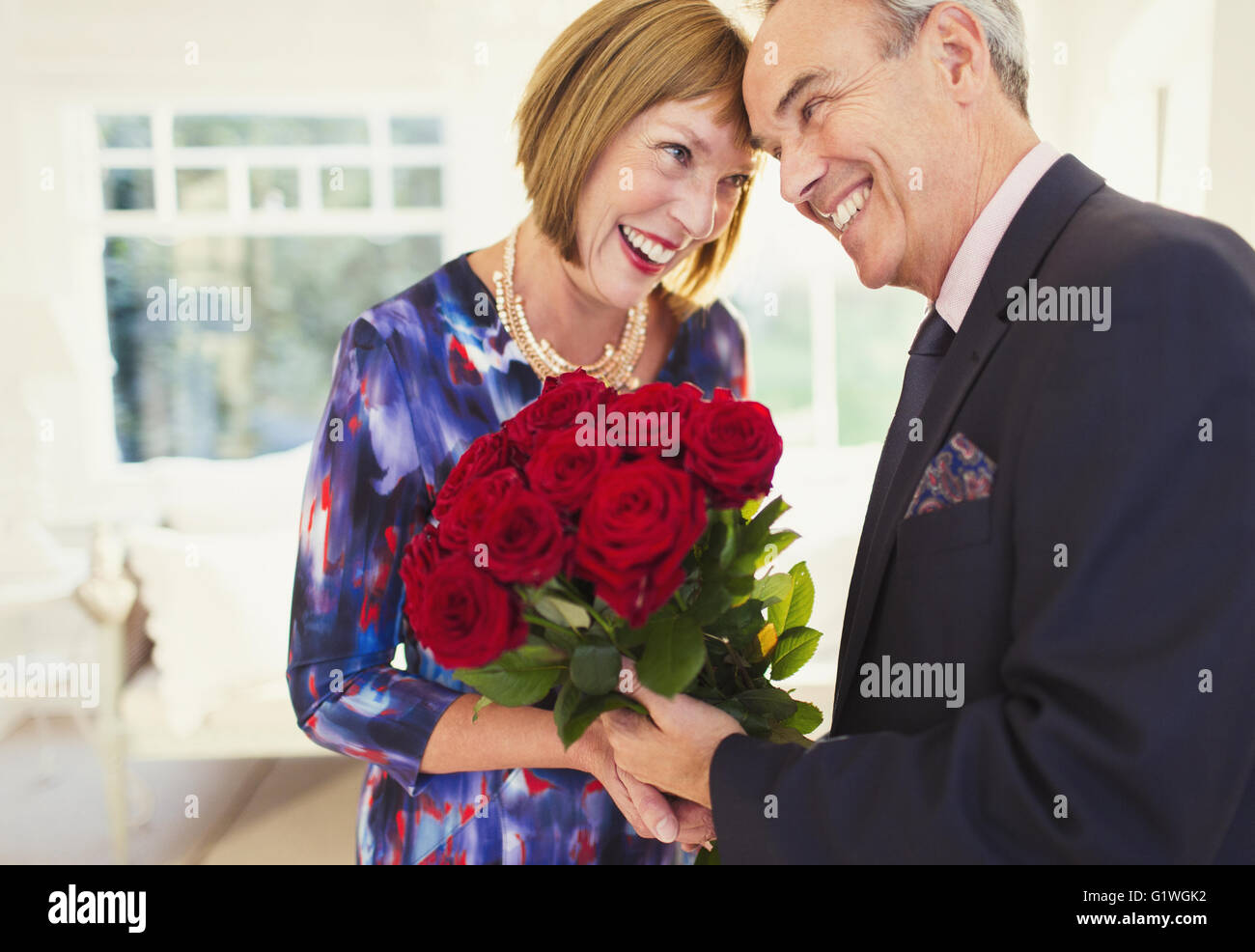 Affectionate well-dressed mature couple with rose bouquet - Stock Image