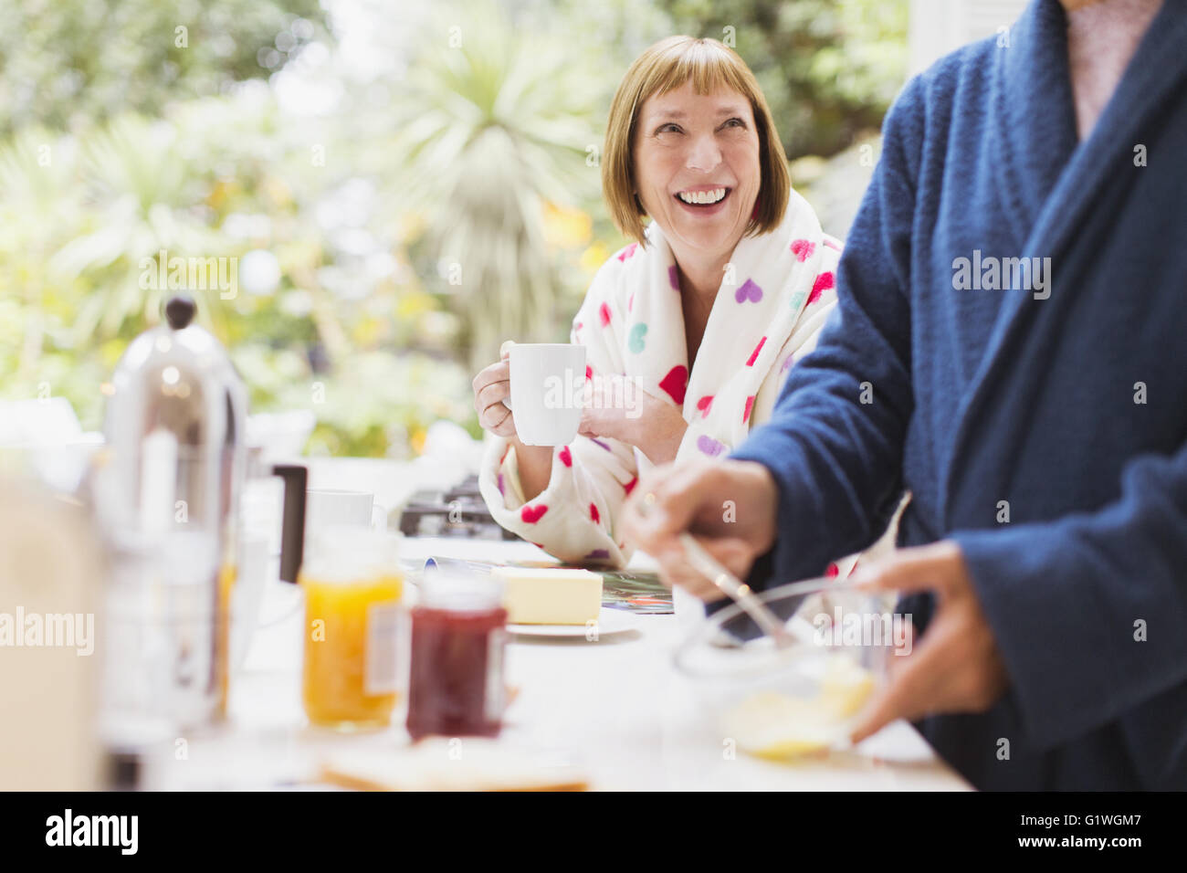 Smiling mature woman drinking coffee in bathrobe at breakfast - Stock Image
