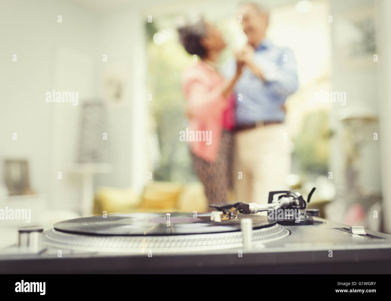 Mature couple dancing in living room behind record player Stock Photo