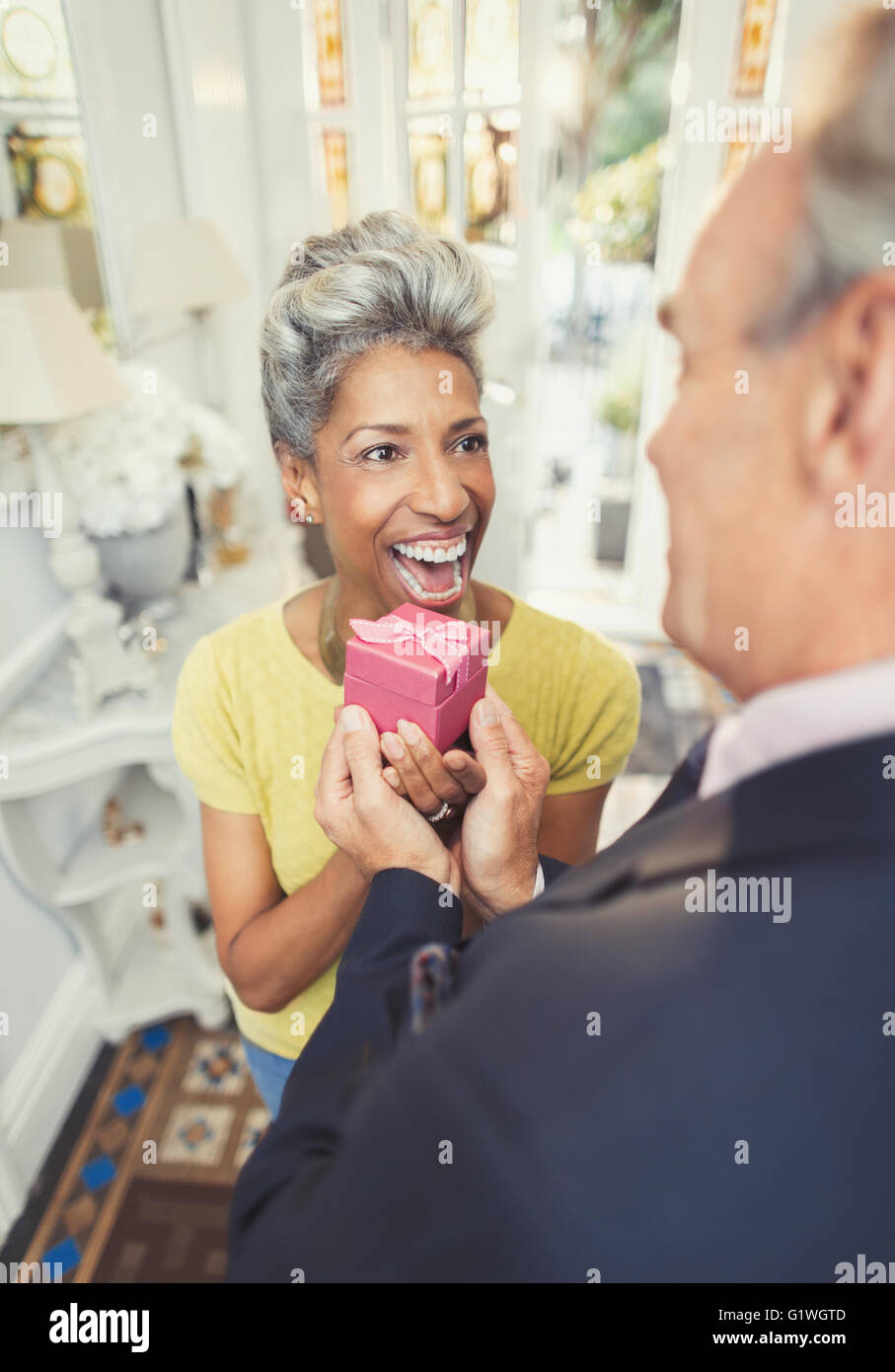 Surprised mature woman receiving gift from husband - Stock Image