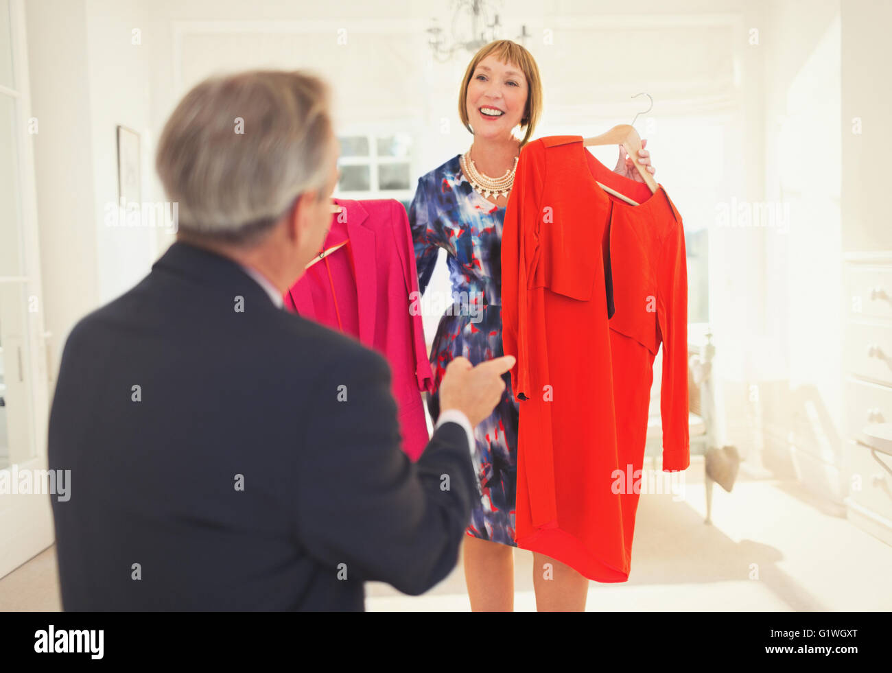 Husband helping wife decide which dress to wear - Stock Image