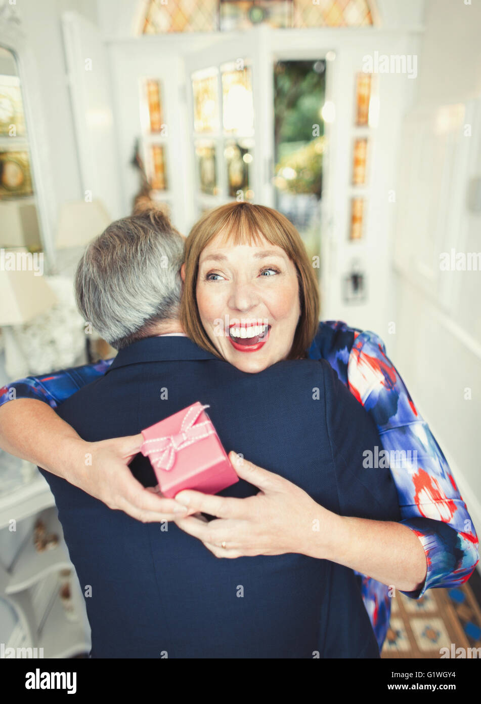 Surprise mature woman receiving gift from husband - Stock Image