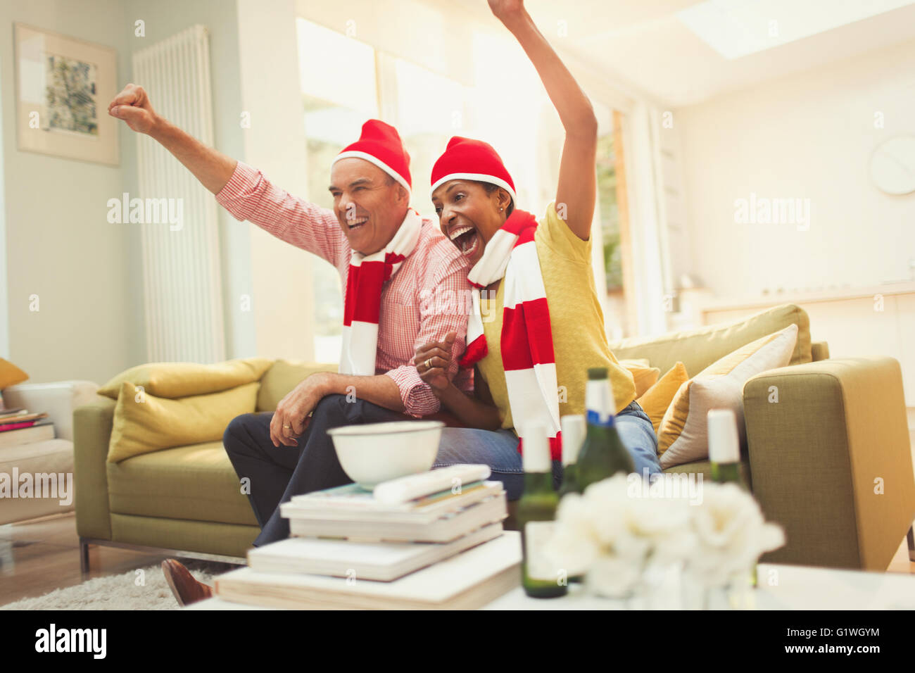 Enthusiastic mature couple in matching hats and scarves cheering watching TV sports event - Stock Image