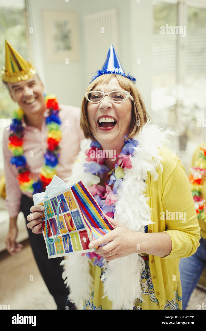 Portrait laughing mature woman in party hat holding birthday gift - Stock Image