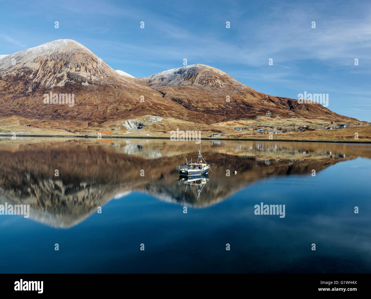 winter mountains at torrin with reflections and mooring boat on loch slapin - Stock Image