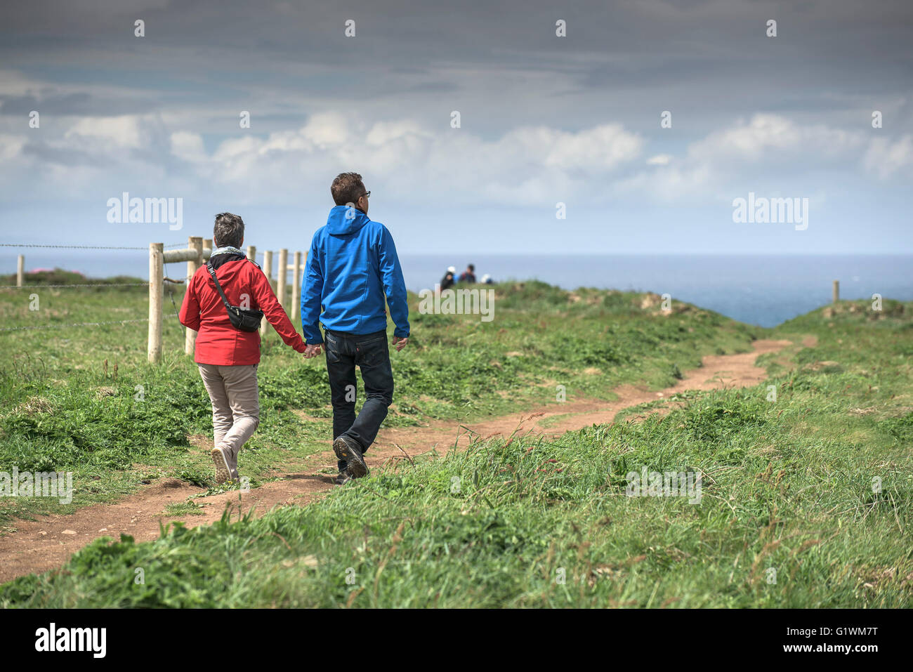 Tourists stroll along the footpaths on the cliffs at Carnewas at Bedruthan in Cornwall. - Stock Image