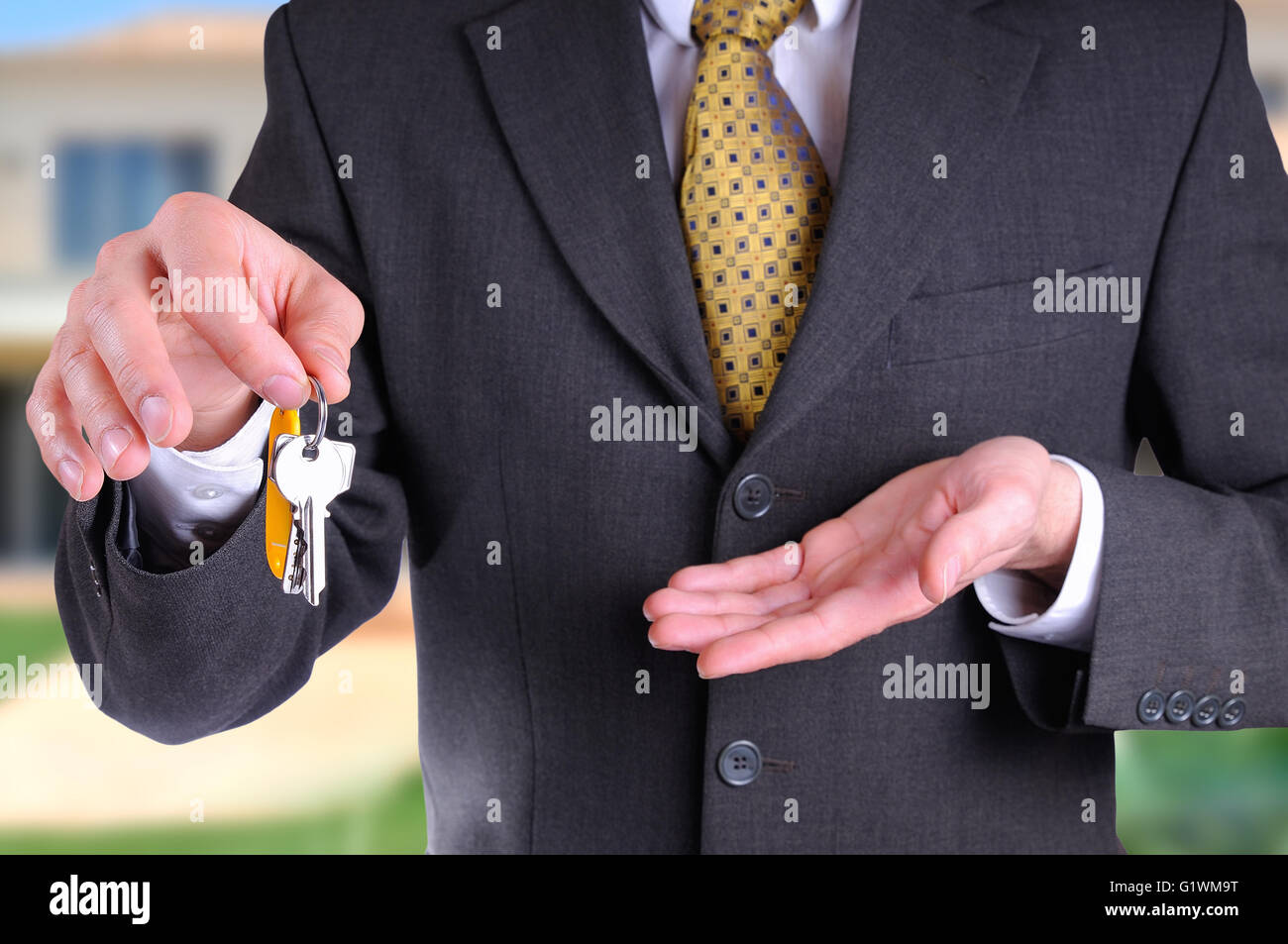Front half-body commercial agent wearing a dark gray costume handing the keys for the purchase of a house with home - Stock Image