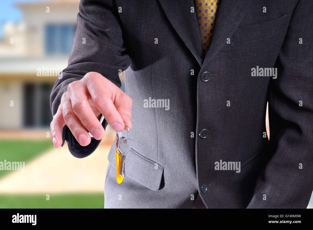 half-body commercial agent wearing a dark gray costume handing the keys for the purchase of a house with home background - Stock Image