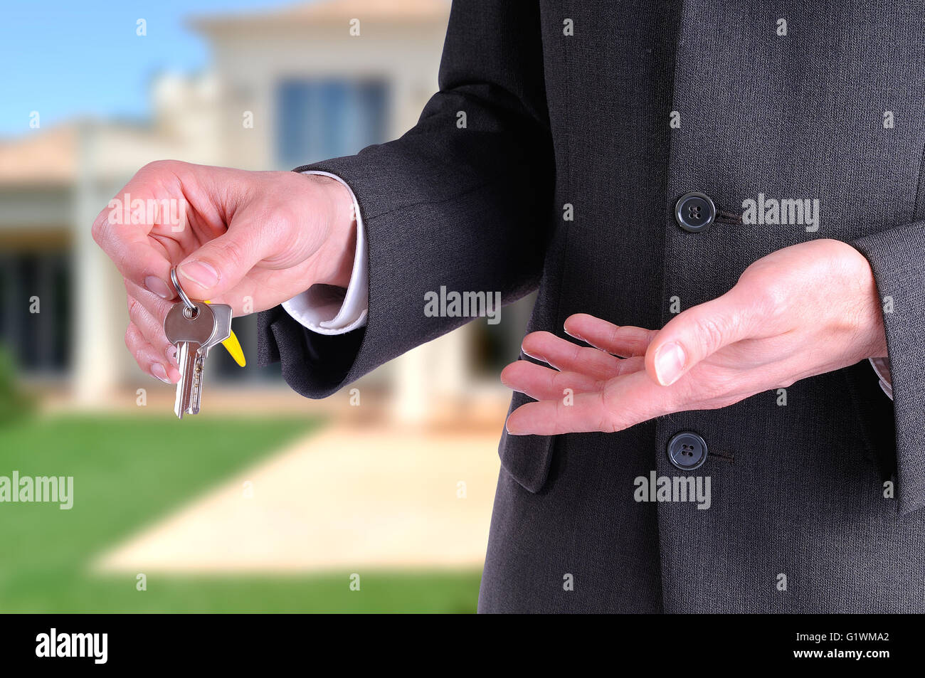 half lateral body commercial agent wearing a dark gray costume handing the keys for the purchase of a house with Stock Photo