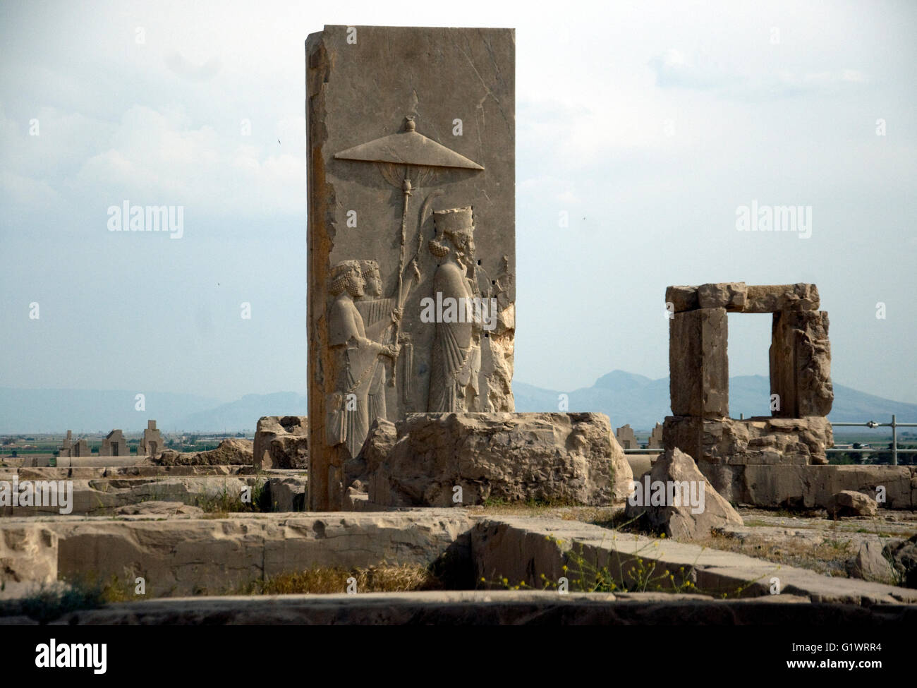 In Iran's grand ruins of a palace complex, Persepolis, a tall carved stone vividly shows ruler and ruled, perhaps - Stock Image