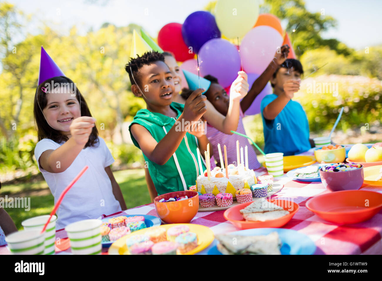 Cute children smiling and having fun during a birthday party - Stock Image