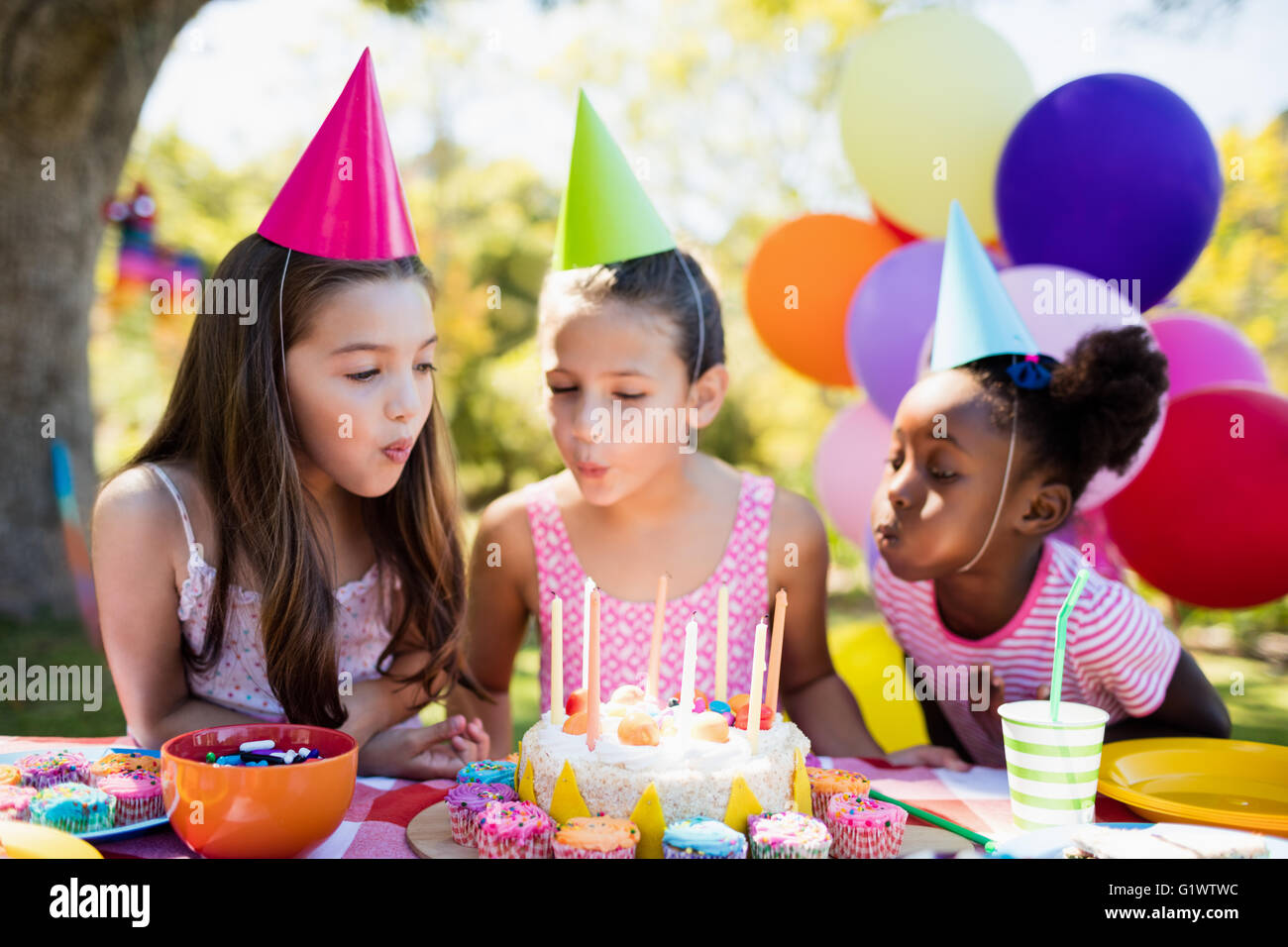 Portrait of cute girls blowing on candle during a birthday party - Stock Image