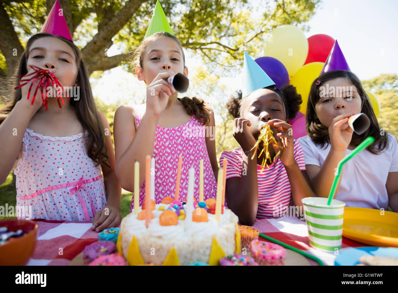 Children breathing out in a birthday trumpets during a birthday party - Stock Image