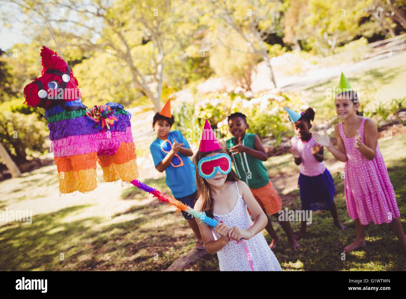 Little girl is going to broke the pinata for their birthday - Stock Image