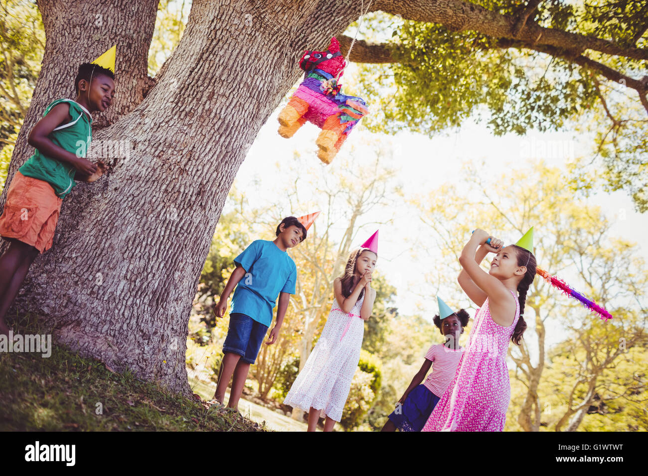 Little girl is going to broke the pinata for her birthday - Stock Image