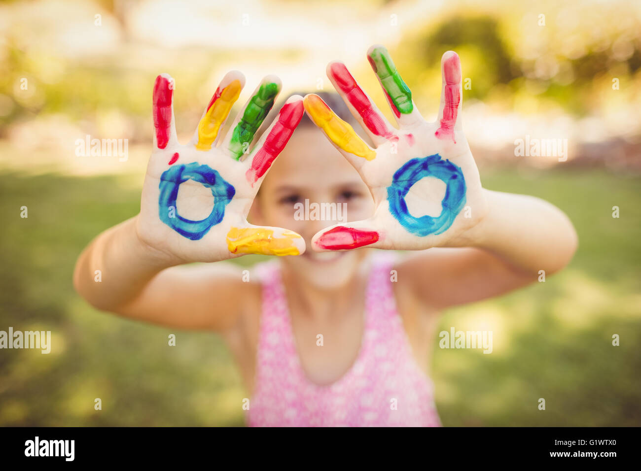 Little girl making a triangle with her painted hands to the camera - Stock Image
