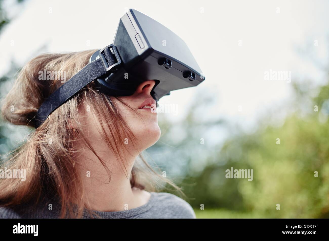 Young woman using a virtual reality headset - Stock Image