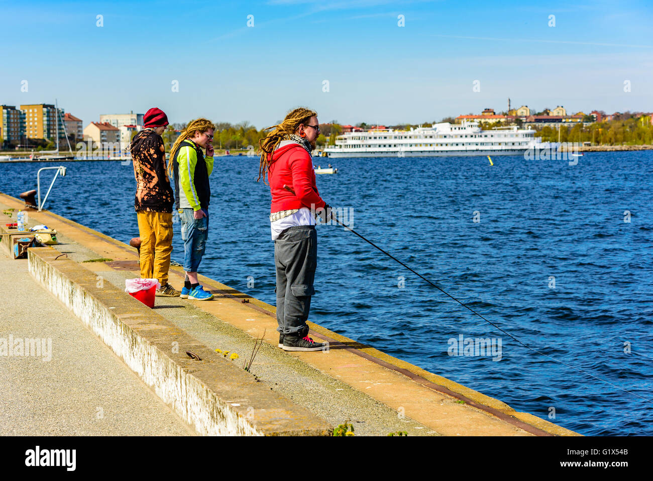 Karlskrona, Sweden - May 3, 2016: Three young adults standing dockside. One is fishing after herring. Two have dreadlocks - Stock Image