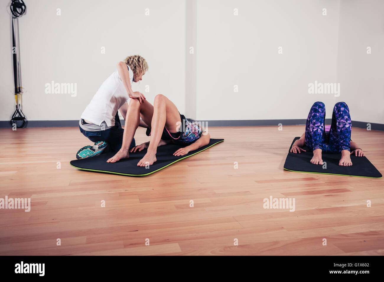 A therapist is correcting the technique of women exercising and stretching in a gym Stock Photo