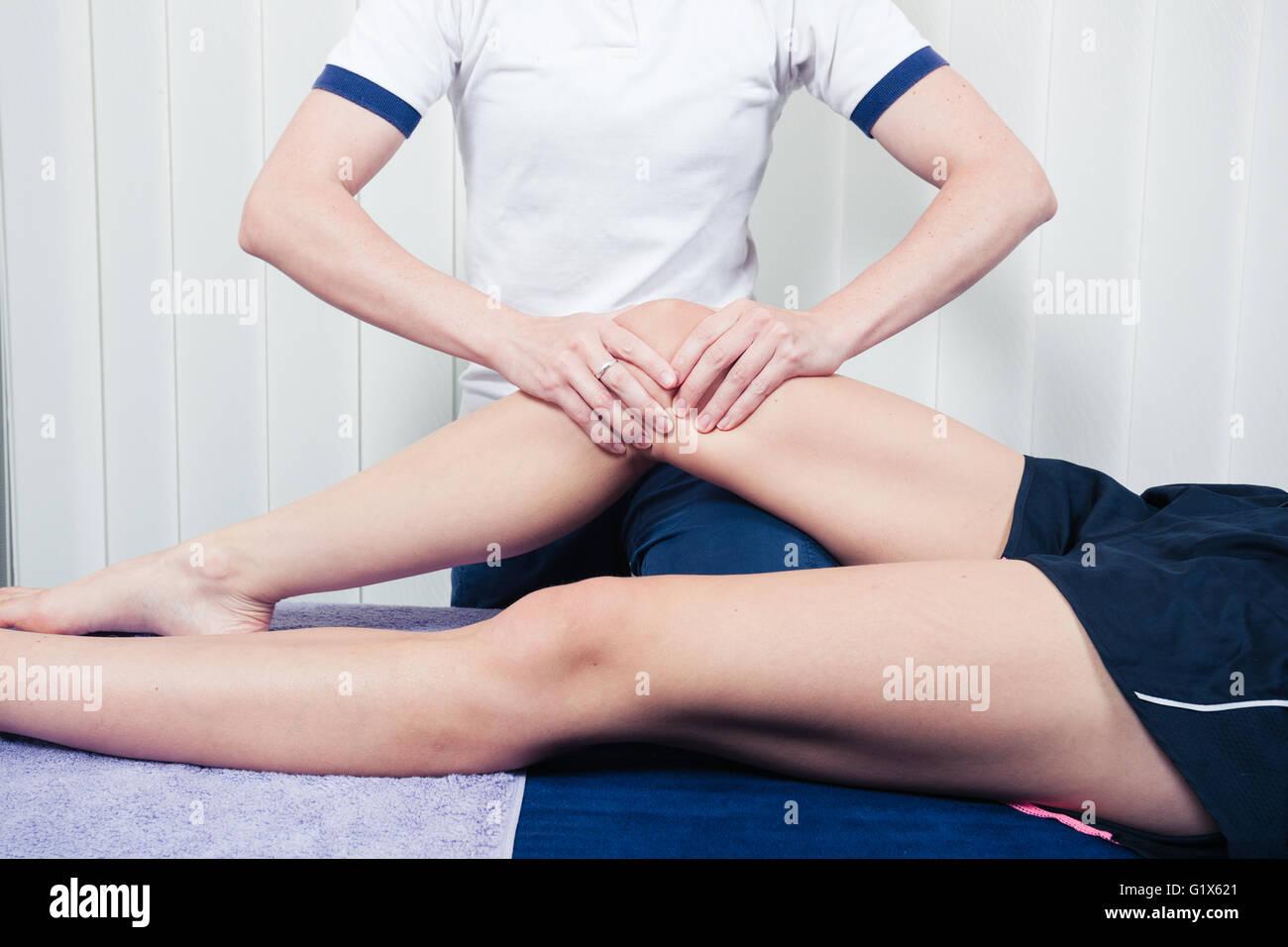 A physiotherapist is treating a patient's knee - Stock Image